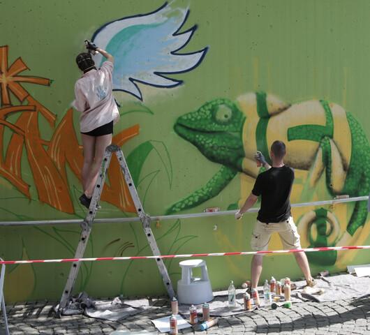 Zwei junge Menshcen stehen an einer Hauswand und sprühen Graffitis, u.a. einen weißen Flügel und ein Chamäleon..