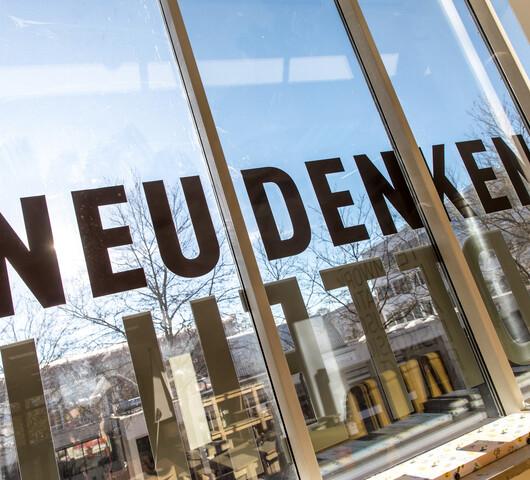 """Eine gespiegelte Fensterfront zeigt den Text """"Neu denken""""."""