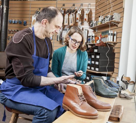 Zwie Menschen sitzen in einer Schusterei und halten Werkzeug in den Händen.
